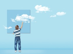 Boy draws with a brush white clouds. Concept image about freedom of mind and thinking outside the box. Freedom concept.