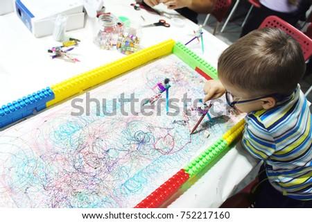 Boy draws with a homemade robot made of pencils #752217160