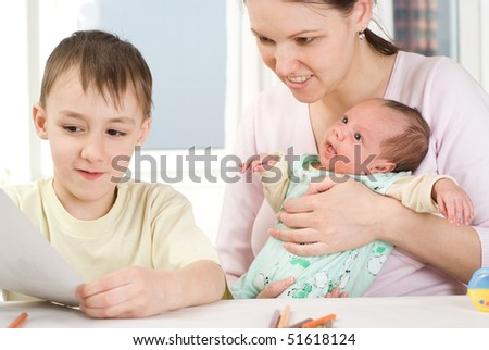 boy draws  with his mother and newborn