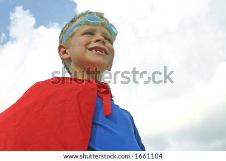 Boy dressed as superhero on cloudy day
