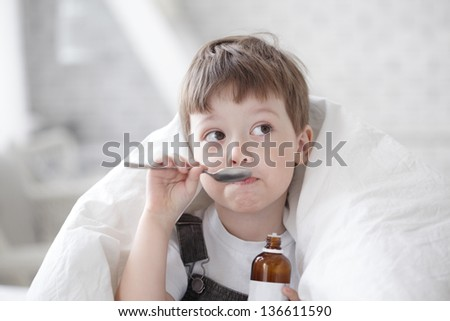 boy drinking cough syrup - stock photo