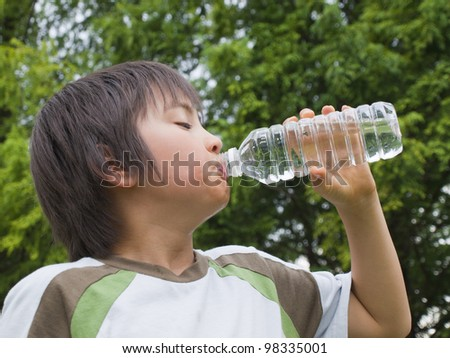 Boy drinking mineral water - stock photo