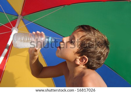 Boy drinking water under the colorful parasol