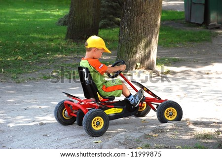 Boy driving a pedal car