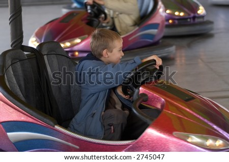Boy driving an electric car in amusement park