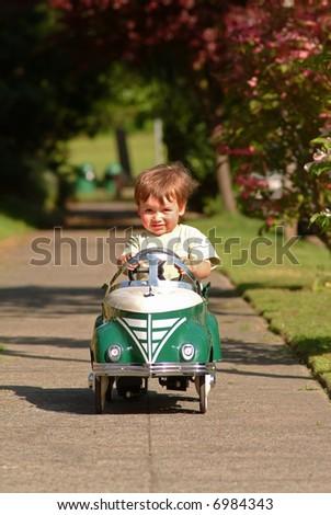 boy driving pedal car