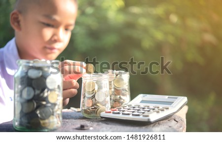 Boy drop money coins to jar. Concept of Insurance money savings, retirement planning ,travel and investment ideas, passive income.education plan,401k plan, Financial freedom.