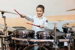 Boy drumming. boy in a white shirt plays the drums. A boy in a white shirt is drumming