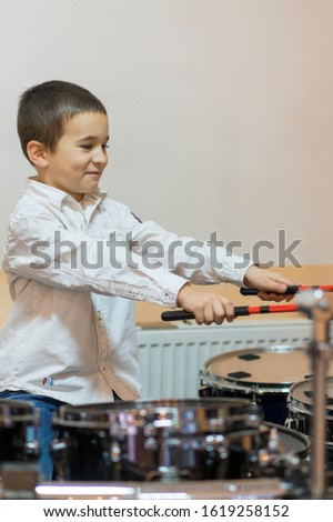 Boy drumming. boy in a white shirt plays the drums. vertical photo