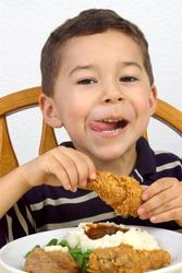 Boy eating a fried chicken dinner