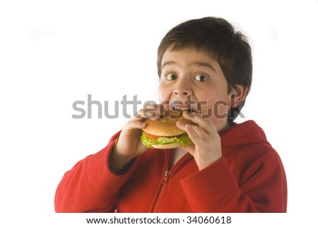 boy eating a sandwich with lettuce and tomato