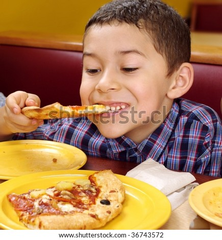 boy eating a slice of pizza, seven years old