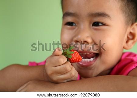 boy eating a very tasty strawberry