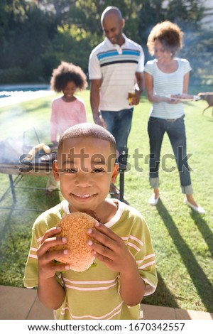 Boy eating burger family at barbeque in garden at camera