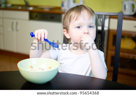 Boy eating cereals  with milk