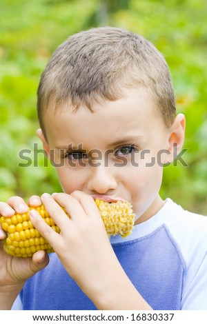 Boy eating fresh boiled corn