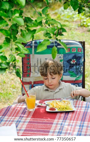 boy eating outdoors - French fries with ketchup