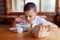 Boy eating soup for dinner in a rustic restaurant outdoor
