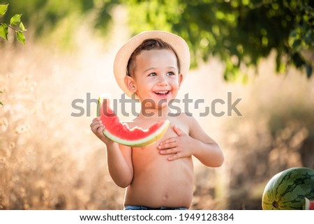 Boy eating water-melon. Funny happy child eating watermelon outdoors. Little boy eating watermelon. Kids eat fruits in the garden