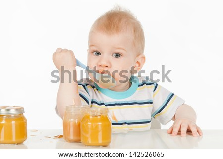 Boy eats with a spoon puree, on a gray background