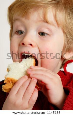 Muchacho que goza de un emparedado de la mantequilla y de lajalea de cacahuete