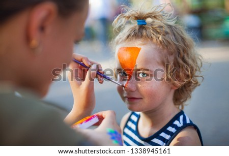 boy face close-up with red colors on his face, face painting watercolor, artist paints watercolor paints tiger mask, draw on the boy's face paints picture, orange ink for drawing the tiger.