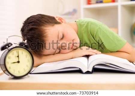 Boy fallen asleep on his book while studying late in the evening