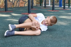 boy fell and hurt himself on the outdoor playground. knee injury child sports injury. boy crying in pain