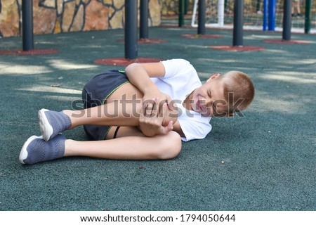 boy fell and hurt himself on the outdoor playground. knee injury child sports injury. boy crying in pain Stockfoto ©