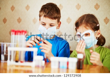Boy fills chemical test tube with specimen and girl sits near to him, focus on boy face