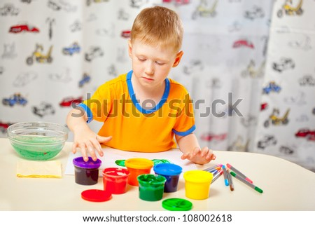 Boy finger paints on paper at his room