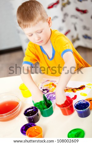 Boy finger paints on paper at his room, vertical photo