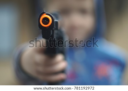 Boy fires with a toy gun pistol. focus on the gun