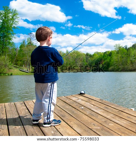 Boy fishing from dock on lake.