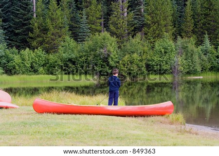 boy fishing in a lake beside his canoe - nice reflection of the trees in the water - adobe RGB - stock photo