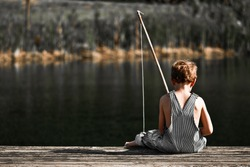 Boy fishing in overalls from a dock on a lake or pond with text space to the left.