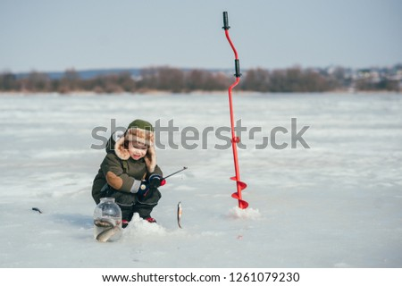 boy fishing on winter. Cute boy catches fish in the winter lake. Winter. Outdoor #1261079230