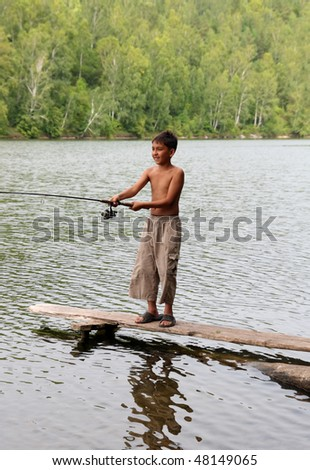 boy fishing with spinning on stage in lake