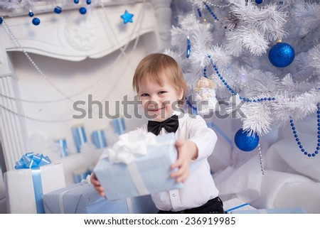 boy five years gives Christmas gift sitting near the Christmas tree