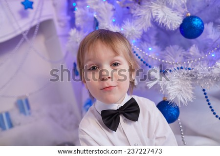 boy five years in anticipation of a gift, sitting near the Christmas tree