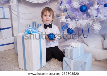 boy five years in anticipation of a gift, sitting near the Christmas tree, holding a blue balloon
