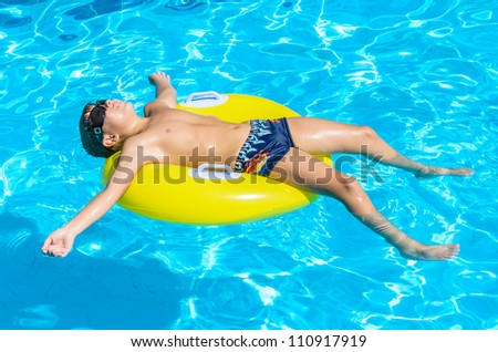 Boy floating on an inflatable circle in the pool. A child in the pool