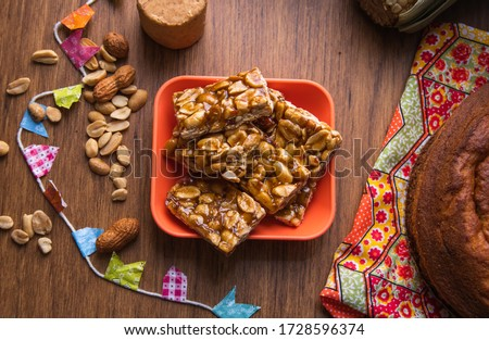 """Boy Foot or """"Pé de Moleque"""" is a Peanut candy tipical in Festa Junina Festival. Traditional food of Brazil, June Party sweet. Arraial Rustic Wood Background."""