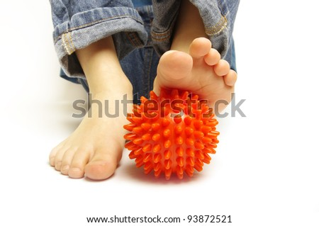 Boy foot with spiny plastic orange massage ball