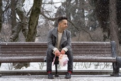 Boy friend with a bouquet of pink flowers hydrangea waiting for his girl friend outdoors while snow is falling. Valetnine`s day concept, wedding proposal. 