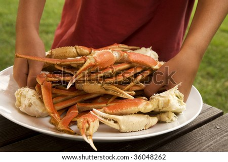 Boy gathering up crab legs off from large serving plate