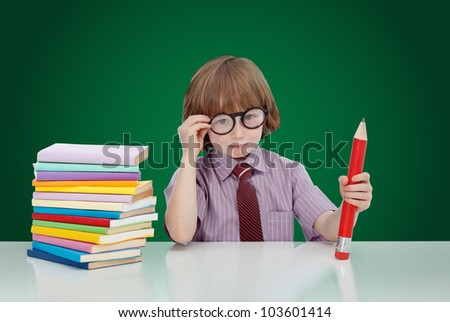 Boy genius with books and large pencil adjusting his glasses - on green background
