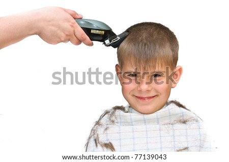 Boy gets haircut. Isolated on white background photo.