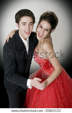 Boy & girl, in formal attire, dancing at their high school prom.