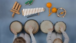Boy girl kids playing orff instruments - Musical instruments for children: drums, flute, metallophone